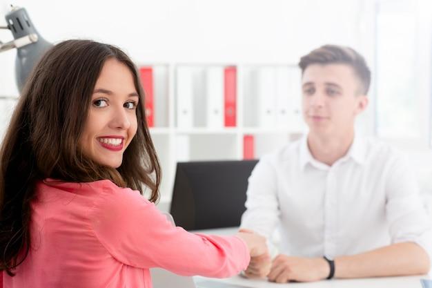 Бизнесмен и бизнес женщина рукопожатие в банке
