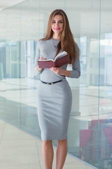 ビジネスの女性が彼女の手で日記を押しながらカメラを見て