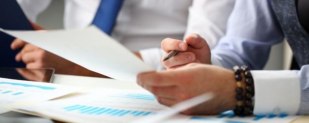 財務グラフと銀のペンを持つビジネスマンのグループ