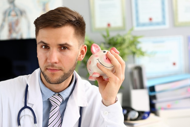 貯金箱を振って医師の肖像画。医師は聴診器で白い制服を着て、病院のオフィスでポーズします。落ち着いてカメラ目線の男。健康保険政策のコンセプト