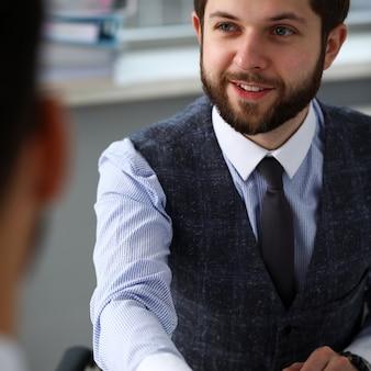 スーツとネクタイの男がオフィスでこんにちはとして手を与える