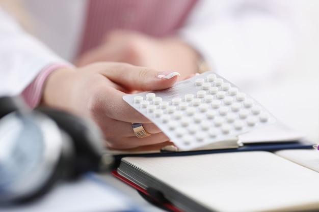 職場のクローズアップで別のタブレット水疱のパックを持っている女性医師の手。万能薬の命を救うサービス処方薬法的ドラッグストア病気癒しの血圧の概念