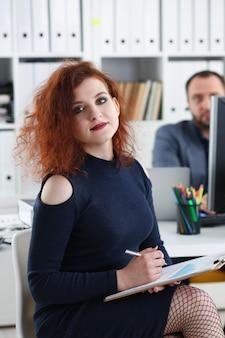 Молодая красивая рыжая женщина сидит за столом в офисе в кабинете ее босс держать ручку в руках