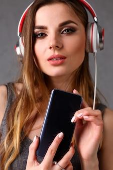 スマートフォンを手に保持しているヘッドフォンの女性。