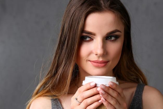 美しい若い笑顔の女性は、お茶の肖像画の白いカップを腕で保持します。寒い日に新しい香りの良い香りの温かい飲み物は、水の現在の概念を開始します