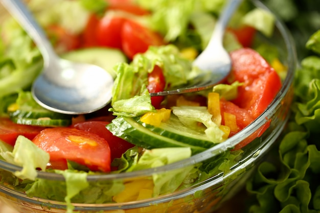 Серебряная вилка и ложка в тарелке смешивают салат со свежими овощами, заправленными оливковым маслом. сыроедение и вегетарианство в современном обществе - популярное понятие.