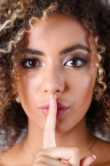 美しい黒人女性の肖像画。彼女は彼女の指で唇を開き、白いロックの目を見て、もっと静かな美しさのファッションスタイルの巻き毛を言う