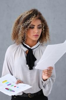 Красивый портрет чернокожей женщины. держит бумажные документы с финансовой статистикой в стиле модных вьющихся волос с белыми прядями с глазком на камеру много работы