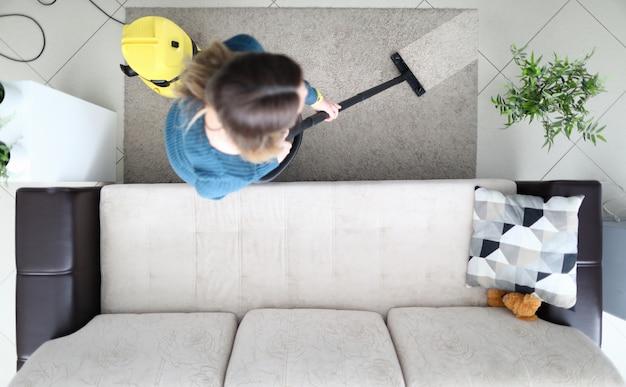 若い女性が自宅で自然光とパステルカラーの家具、上面の掃除機でカーペットを掃除します。クリーニングサービスと近代的な掃除機のコンセプト