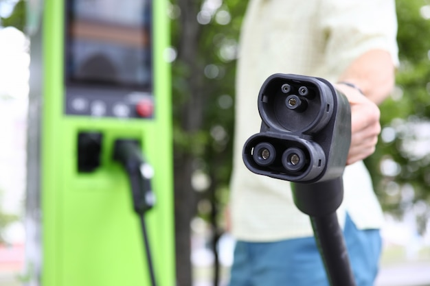 Мужской рукой, придерживая черный автомобиль зарядки автомобильного кабеля
