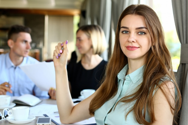 美しい笑顔の陽気な女の子ホールドシルバーペン