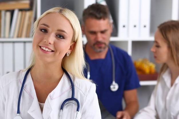 Красивая улыбающаяся женщина-врач в кабинете