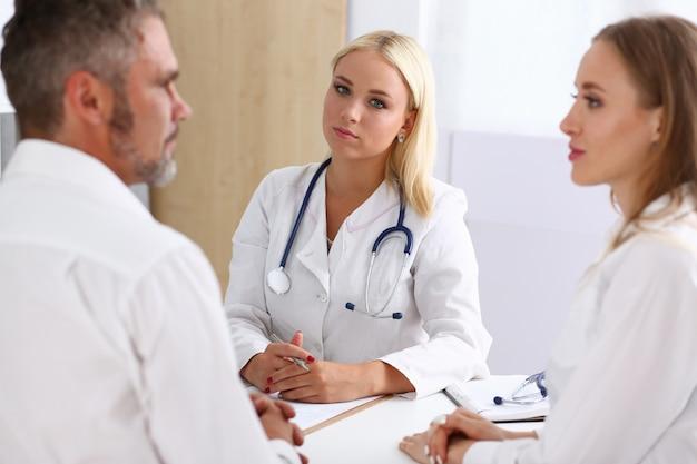 Женский семейный врач внимательно слушает молодая пара