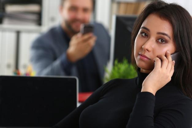 彼女の上司と事務作業で若いかなりブルネットの女性は手でスマートフォンを保持します。