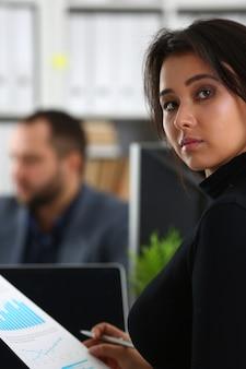 若くてきれいな女性が彼女のボスのキャビネットのオフィスのテーブルで椅子に座る腕の中でバインダーを保持します。