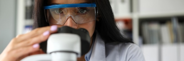 Лаборант с помощью микроскопа