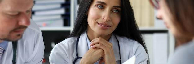 オフィスで若い女性に相談する医師のグループ