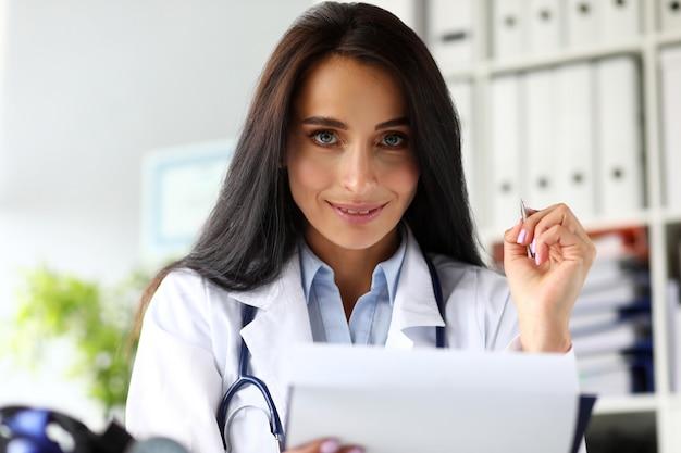 Довольно женщина-врач держит в руках блокнот