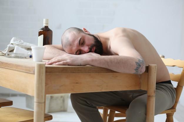アルコール男はアパートのテーブルで眠りに落ちた