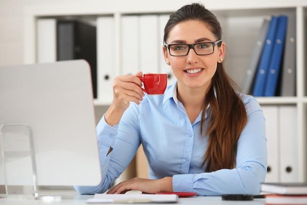 ビジネスの女性は、赤いマグカップからテーブルでオフィスでコーヒーを飲む