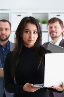 Брюнетка женщина держит ноутбук со своими коллегами