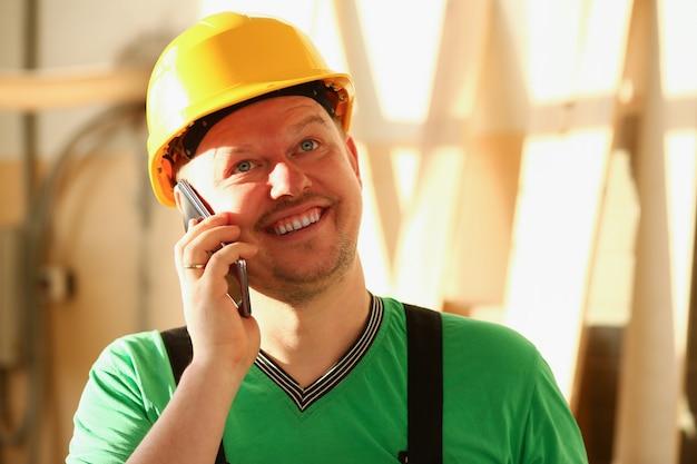 大工は金物屋で電話で話しています。