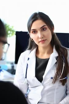 患者と話しているブルネットの女性医師
