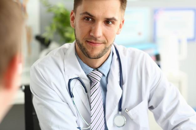 Улыбающийся специалист клиники разговаривает с пациентом