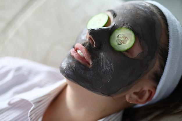 顔のマスクを持つ女性