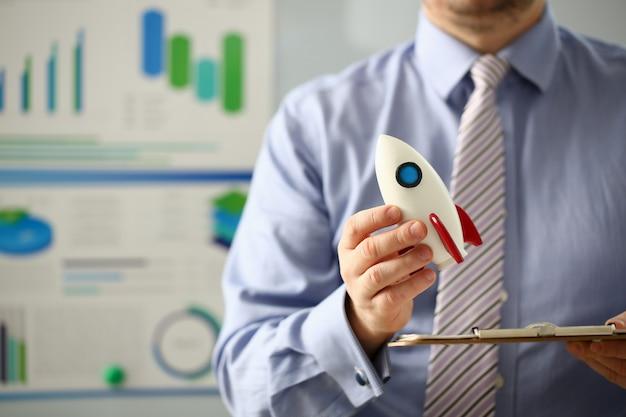 スーツのビジネスマンが手に白いロケットを保持するオフィス