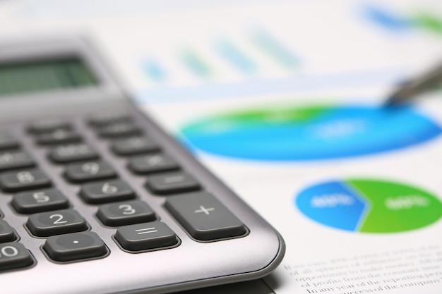 Серебряный калькулятор и финансовая статистика на буфер обмена площадку на офисном столе крупным планом.