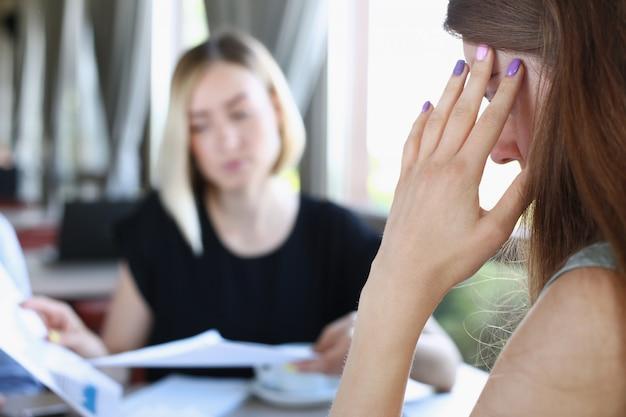 ビジネスの女性は頭に彼女の手を保持しています。