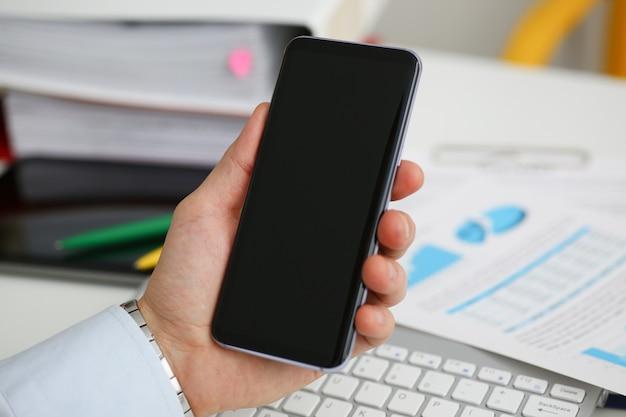 Бизнесмен держит новый телефон