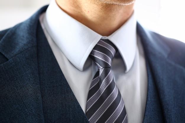 青いスーツの男性の腕セットネクタイクローズアップ
