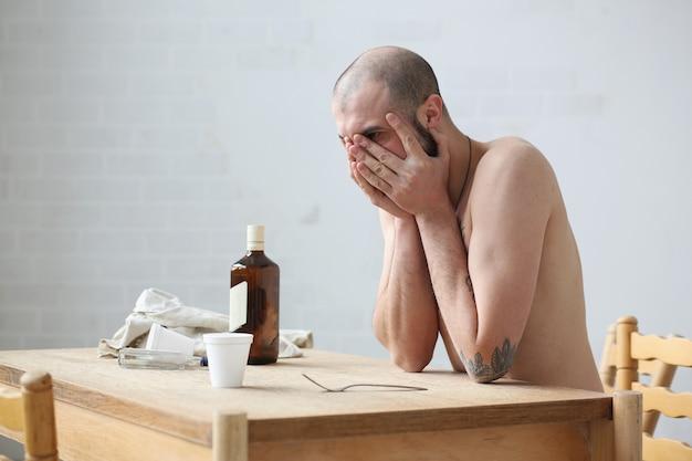 ロシア人はテーブルに座って酔って悲しい。彼は彼女の顔を閉じます