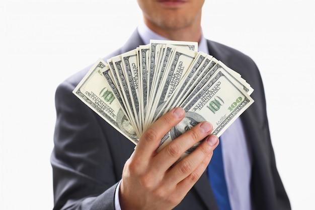 スーツを着た男がお金を保持します。