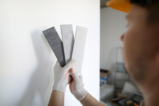 白い保護手袋の男性ビルダーは灰色のトーンを保持します