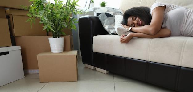 Надоело готовится к переезду, женщина спит на диване.