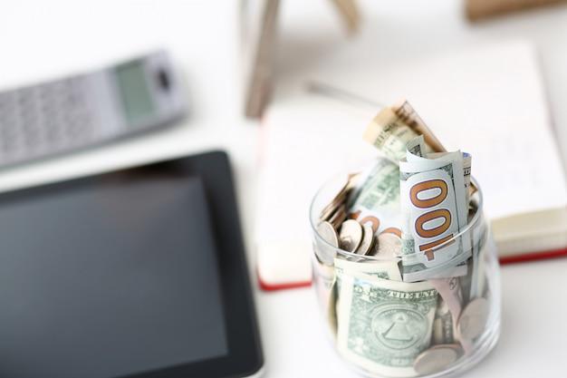 Большая банка с банкнотами и монетами сша стоит на пустом рабочем столе