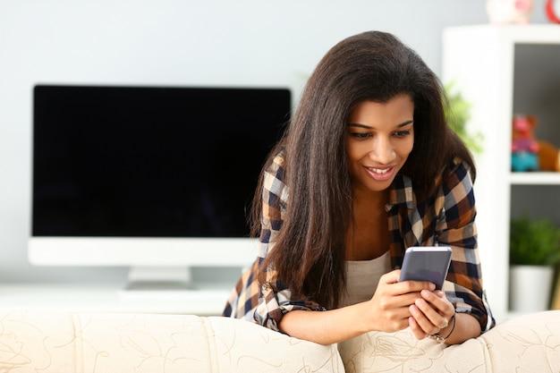 笑顔の黒人女性が自宅で携帯電話を手に保持します。