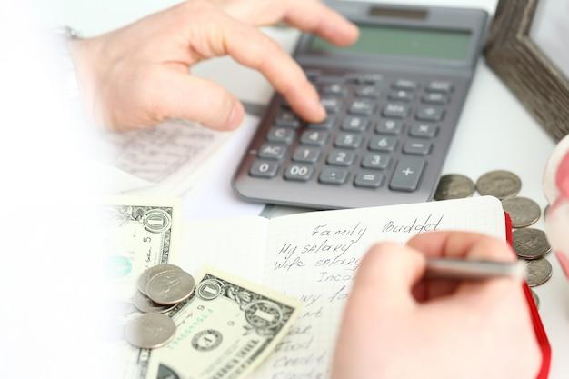 Мужская рука делает заметки в красном блокноте о семейном бюджете, оценивая расходы