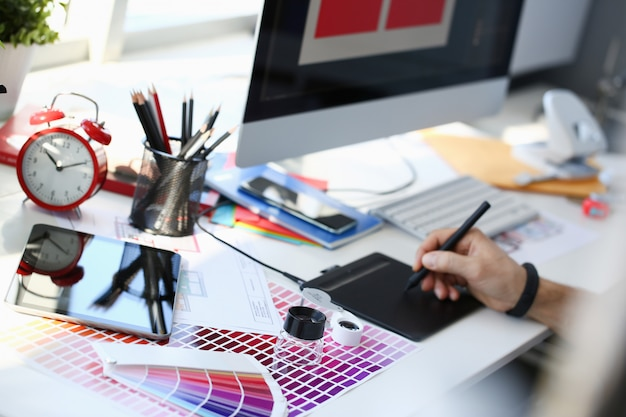 Дизайнер мужской руки держит графический блокнот работает над проектом