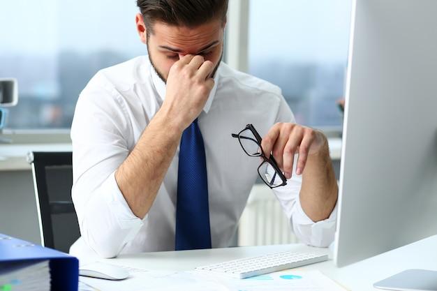 Усталый клерк на ноутбуке на рабочем месте в очках