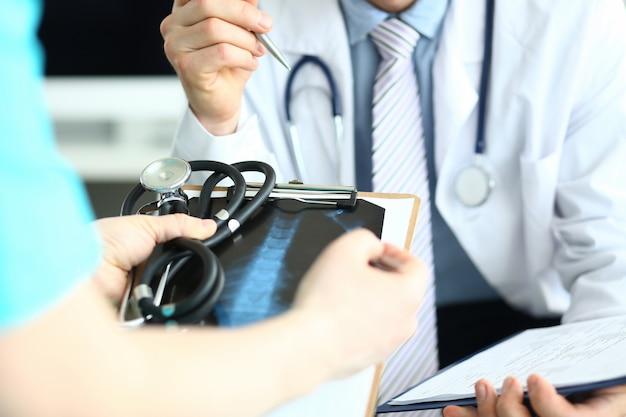 医師のグループは、適切な治療法を選択する患者の履歴とともにクリップボードを手に保持します