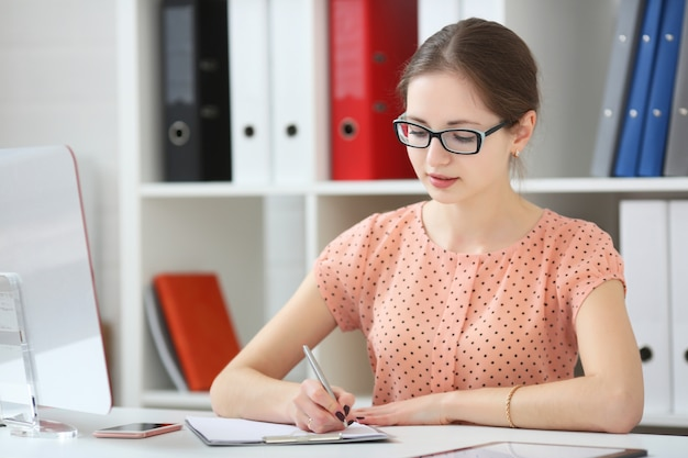 オフィスの女性は日記にメモを取る