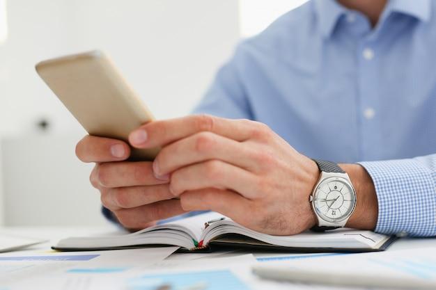 ビジネスマンは彼の手で新しい携帯電話を保持します