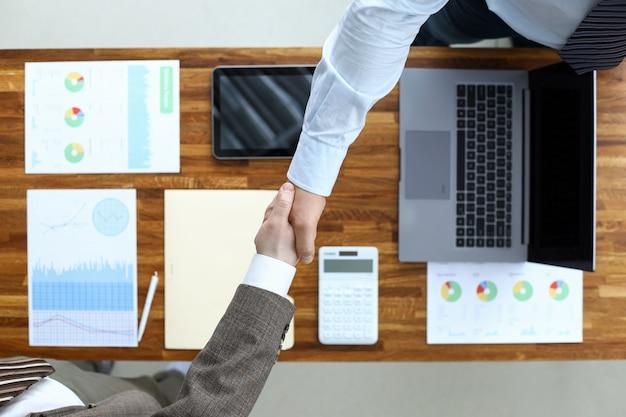 Мужчины пожимают друг другу руки за столом в кабинете, договариваются. программы действий по развитию. стратегические планы развития предприятия. проект и получение необходимых ресурсов для него