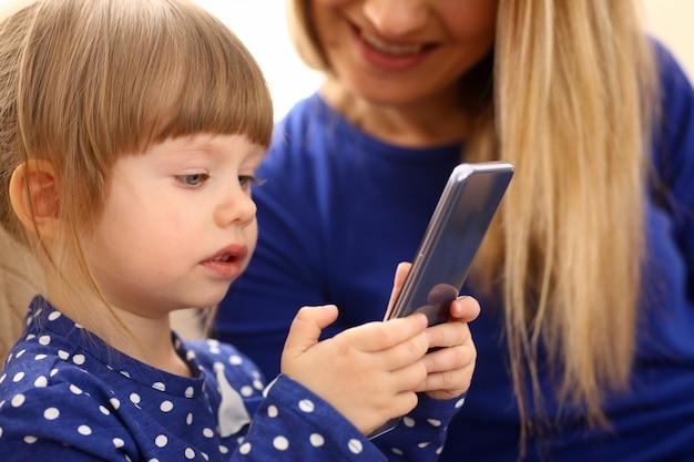 Милая маленькая девочка на полу ковер с мамой
