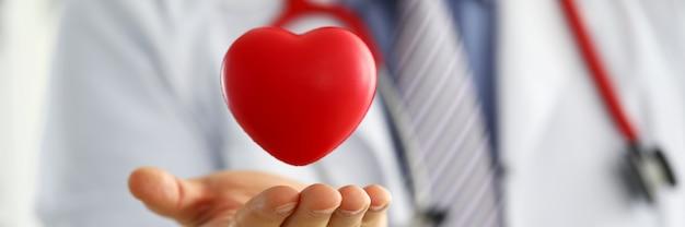 男性医学博士の手を保持し、赤いおもちゃの心をカバー