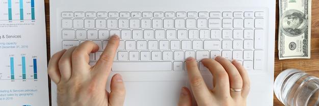 Мужские руки, набрав текст на клавиатуре ноутбука
